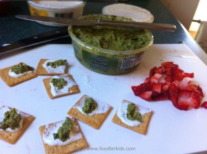 Crackers with basil pesto, garlic mint cheese, and diced strawberries