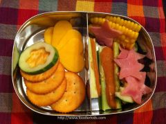 Cheese, crackers, cucmbers, peanut butter celery sticks, ham stars, and corn in the Lunchbots pico.