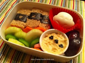 Hard-boiled car egg, hummus with car nori decorations, sandwich wedges wrapped in nori