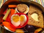 Hard-boiled heart egg, hummus cup topped with heart bread slice, sandwich with heart cut-out, fruit and veggies