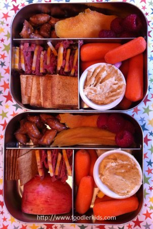 pastrami, cheese, crackers, carrots, hummus, apple, dried mango and pretzel nuggets
