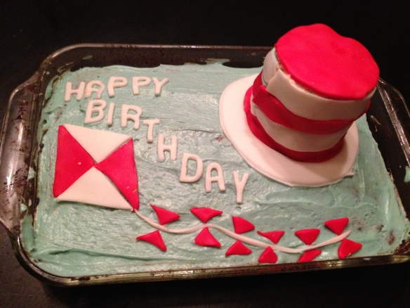 "Chocolate Cake frosted with blue-tinted butter cream. Topped with fondant kites and ""Happy Birthday."" Plus a fondant-wrapped mini cake made to look like a red and white striped hat."