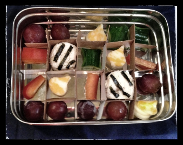 "Chicken circles and seaweed ""special candies"", red pepper, grapes, cheese, inserted into grid"